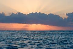 Calm ocean on tropical sunrise. Calm ocean and sun behind clouds on tropical sunrise Stock Photo