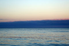 Calm ocean waters of Waimanalo Bay at dusk with clouds hanging o Stock Photo