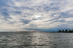 Calm ocean on a wonderful afternoon with a cloudy sky. With white and blue clouds with the city of Volendam on the horizon in the Netherlands stock image