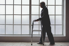 Calm old woman holding foldable walker in room of clinic Stock Photos