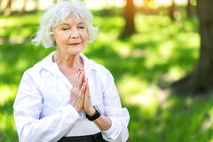 Calm old woman meditating in green park. Waist up portrait of restful elderly lady performing yoga position among summer forest trees. She is closing her eyes Stock Image