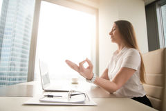 Calm peaceful businesswoman practicing yoga at work, meditating. Calm peaceful businesswoman practicing yoga at office desk sitting near laptop, hand in chin Stock Photos