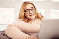 Contented ginger plus-size woman wearing clear glasses. Calm and peaceful. Contented ginger plus-size woman wearing clear glasses while resting in her living stock photography
