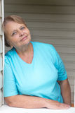 Calm and peaceful pensioner woman at window Stock Images