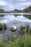 Calm and peaceful Sylvan Lake. A small log sits in the foreground of the famous Sylvan Lake near Custer, South Dakota Royalty Free Stock Images