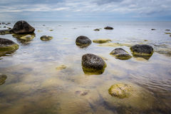 Calm an peaceful view of stones with seaweed. Stock Photo