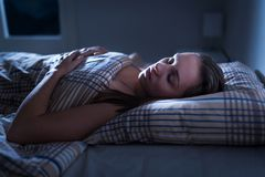 Calm and peaceful woman sleeping in bed in dark bedroom. Lady asleep at home in the middle of the night. royalty free stock images