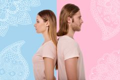 Calm people standing with their backs touching and thinking about music. Music fans. Young serious couple standing behind each other and looking thoughtful after stock images