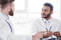 Calm physician listening his associate during colloquy. Serene bearded asian doctor hearing affiliate in apartment of clinic during meeting royalty free stock images