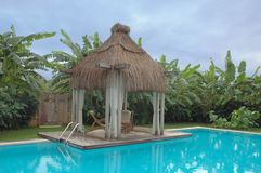 Calm place. Magic corner of the private villa: bungalow, palm trees and waterpool Royalty Free Stock Photography