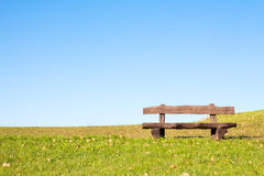Calm place to rest and relax. A calm place to rest and relax. An empty wooden bench  over a serene blue sky waiting for a hiker or casual walker to sit and rest Stock Photo
