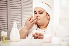 Calm plus-size lady wearing bathrobe and hair bandage. Overweight woman checking. Calm plus-size lady wearing bathrobe and hair bandage while smelling her stock images