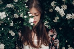 Calm portrait of beautiful hipster woman in blooming bush with w. Hite flowers of spirea. boho girl sensual portrait in floral modern clothes in greenery. space stock photo