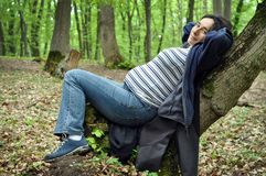 Calm pregnant woman relaxing in the forest Stock Photos