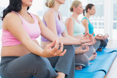 Calm pregnant women meditating in yoga class Royalty Free Stock Images