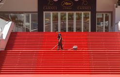 CANNES, FRANCE — MAY 19, 2017: A man vacuums the iconic red carpet steps ahead of festivities at the Cannes Film Festival.