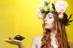 Calm pretty girl with snail and flower crown Stock Photography