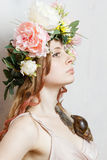 Calm pretty girl with snail and flower crown. On head on white background Stock Photos