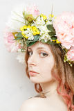 Calm pretty girl with snail and flower crown. On head on white background Stock Photography