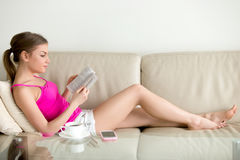 Female book lover reading bestseller book at home Stock Photography