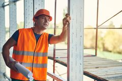 Curious builder touching the incomplete construction and holding drawings. Calm professional builder in orange uniform standing with drawings and thoughtfully stock photos