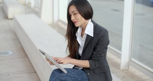 Calm professional woman using tablet. Calm and beautiful professional female sitting outside in front of building using a tablet computer and looking over stock video footage
