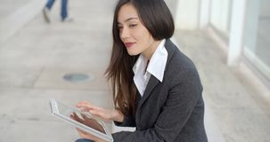 Calm professional woman using tablet. Calm and beautiful professional female sitting outside in front of building using a tablet computer and looking over stock footage