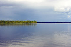 Calm after the rain over the northern lake surrounded by mountains Royalty Free Stock Images