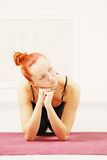 Calm redhead sitting on a mat Royalty Free Stock Image