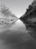 Calm Reflective River. Black and white of a straight calm reflective river in Texas royalty free stock images