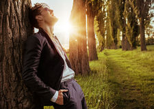 Calm, relaxed man leaning on the tree Royalty Free Stock Image