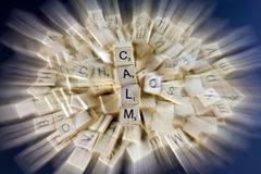Calm Rising From Chaos. Zooming blur of Scrabble tiles with chaos in the middle and tiles spelling calm hovering above in clear focus Stock Image