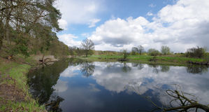 Calm river bend with reflection of cloudy sky Royalty Free Stock Photography