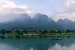 Calm river with boats in the National Park of Phong Nha Ke Bang, Vietnam. Beautiful sunrise with hanging clouds in the hills. stock photo