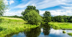 Calm river with meadows and forest around - landscape. Calm river with green meadows and forest around - landscape royalty free stock photo