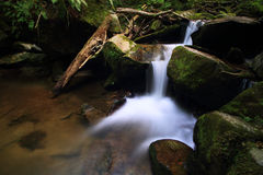 Calm river in the middle of forest. Long exposure photo of the river and it's little waterfall that runs between the large stones using royalty free stock images