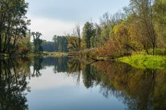 Calm river and reflecting colorful trees in autumn Royalty Free Stock Photography