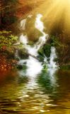 Calm river,waterfall and sun rays in deep wood. stock image
