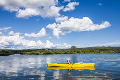 Calm River and Woman relaxing in a Kayak Stock Image