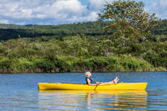 Calm River and Woman relaxing in a Kayak Stock Images