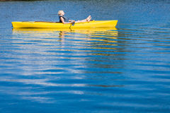 Calm River and Woman relaxing in a Kayak Royalty Free Stock Photography