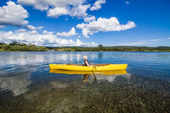 Calm River and Woman relaxing in a Kayak Royalty Free Stock Image