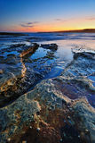 Calm rocks seascape. Sunrise seascape with orange rocks and ocean pools and sea shells with clean bright sky and distant city lights Stock Photography