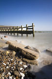 Calm rocky beach at Seaford in the sunshine. Long exposure taken at Cuckmere Haven in Seaford in Summer. With misty soft waters and rocky beach Royalty Free Stock Photo