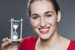 Calm 20s girl with symbol of timing in hands Royalty Free Stock Photography