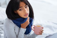 Calm sad woman feeling unhappy and miserable. Feeling miserable. Beautiful young sad woman thinking about her health while drinking hot tea at home stock photography