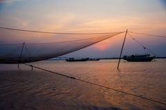 Calm scene of fishing net against purple sunset Royalty Free Stock Photo