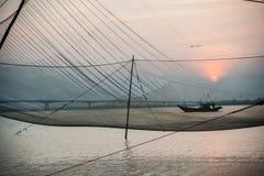 Calm scene of fishing net against purple sunset Royalty Free Stock Photos
