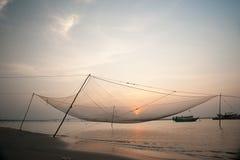 Calm scene of fishing net against purple sunset Stock Images
