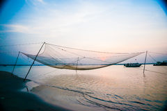 Calm scene of fishing net against purple sunset Stock Photos